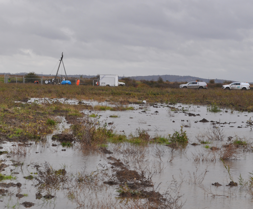 Lower Thames Crossing Ground Investigation Site Visit - View across a very wet and muddy field. Workers carrying out Ground Investigation work in the distance