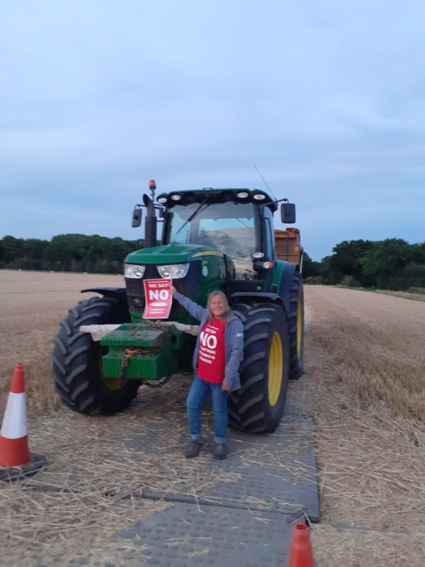 TCAG say NO to the LTC impacts on farming. Photo of TCAG VIce Chair, LEigh Hughes wearing a bright red 'No to LTC' campagin t-shirt, holding a 'No to LTC' poster in front of a local farmer's tractor